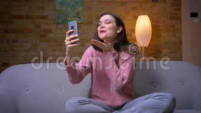 Tiro del primo piano di giovane femmina caucasica castana graziosa che ha una video chiamata sul telefono e seduta sorridente sul stock footage