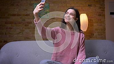 Tiro do close up da fêmea caucasiano moreno bonita nova que toma selfies no telefone e o assento de sorriso no sofá dentro vídeos de arquivo
