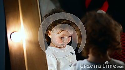 Tiro do close-up A menina está no espelho e olha um bocado tímido vídeos de arquivo