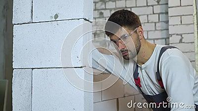 Tiro inclinable del constructor joven en pared de pulido del bloque del desgaste del trabajo con la herramienta abrasiva metrajes