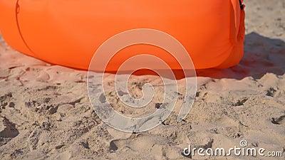 Tiro Slowmotion de uma jovem mulher em uma praia tropical que senta-se em um sofá inflável Conceito das f?rias de ver?o video estoque