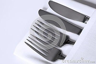 Tischbesteck und weißes Leinen