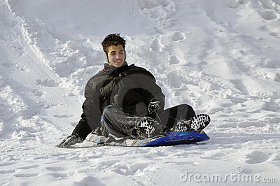 Hispanic teenager ending his slide on a winter day