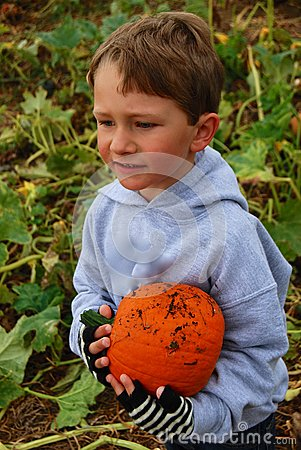 Toddler Boy with an orange pumpkin