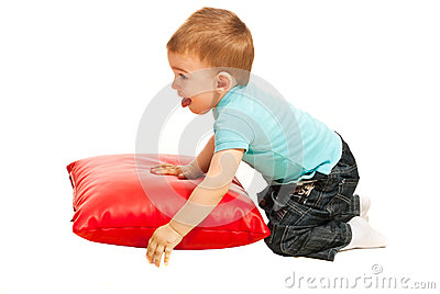 Toddler boy playing with pillow