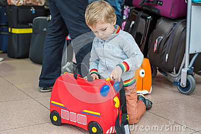 Toddler boy with red child suitcase at airport