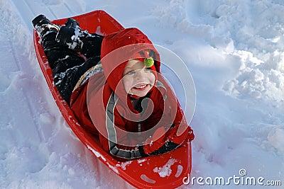 Toddler boy sledding in the snow