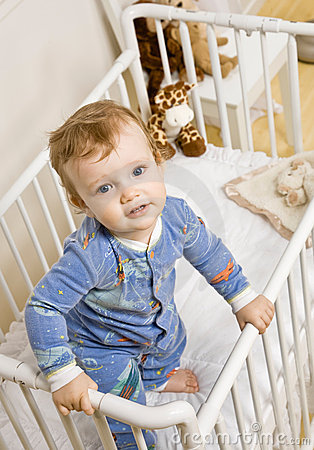 Toddler boy trying to climb out of crib