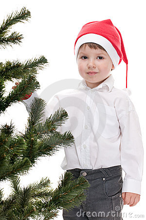 Toddler in christmas hat decorating new year tree