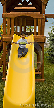 Toddler Coming Down a Slide From a Treehouse