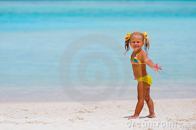 Toddler cute girl standing on tropical beach