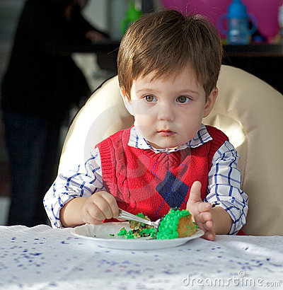 Toddler eating his birthday cake
