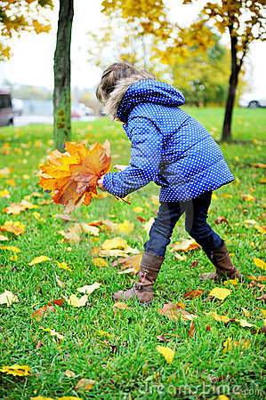 Toddler girl in blue coat picking up leaves