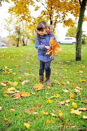 Toddler girl in blue coat picking up leaves