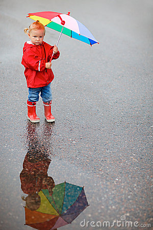 Toddler girl with colorful umbrella on rainy day