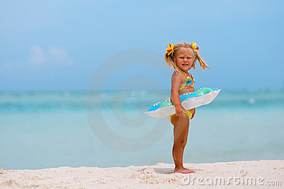 Toddler girl with Inflatable circle on beach