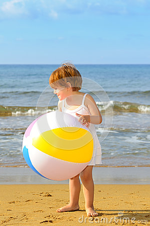 Toddler girl playing with her inflatable ball at beach