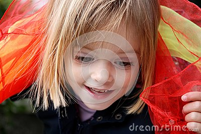 Toddler girl plays with silk scarfs Stock Photo