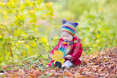 Toddler girl in a red coat playing with red leaves