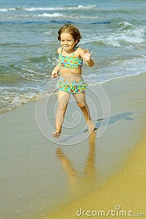 Toddler girl running at beach