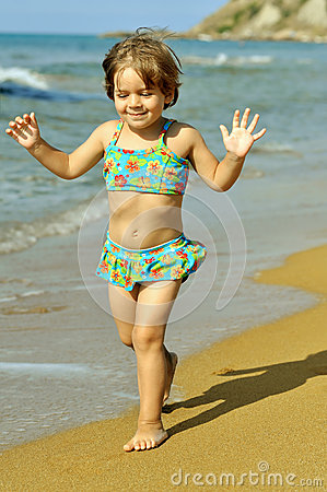 Toddler girl running at beach