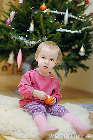 Toddler girl sitting under the Christmas tree