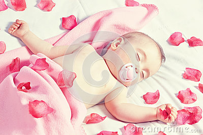 Toddler girl sleeping in a bed strewn with rose petals .