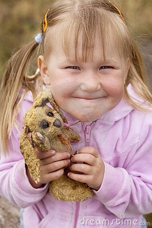 Toddler girl smiling with a bunny toy