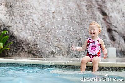 Toddler girl splashing in swimming pool