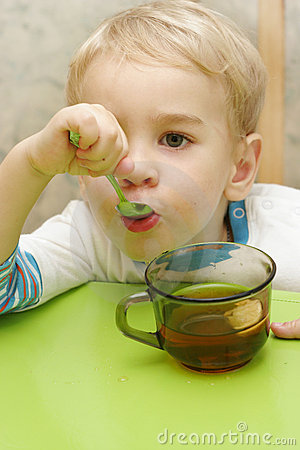 Toddler holding teaspoon in his mouth