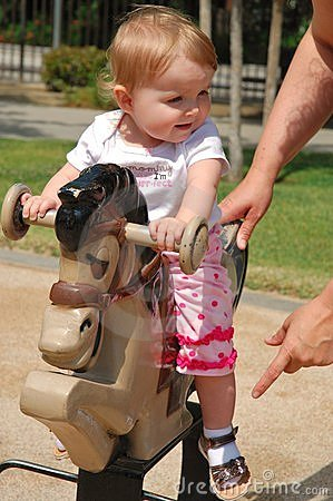 Toddler playing on horse tetter-totter