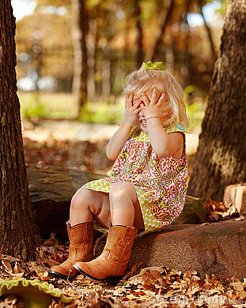 Toddler playing peek-a-boo outside on rock