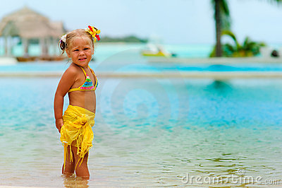 Toddler pretty girl in bikini standing on tropical
