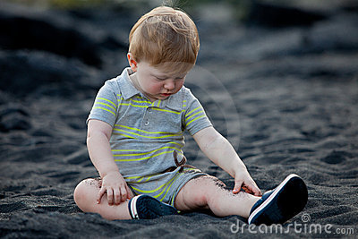 Toddler sitting on black sand beach
