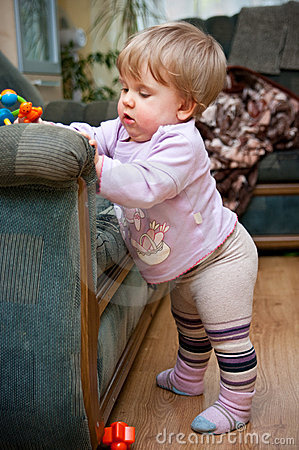 Toddler standing by chair