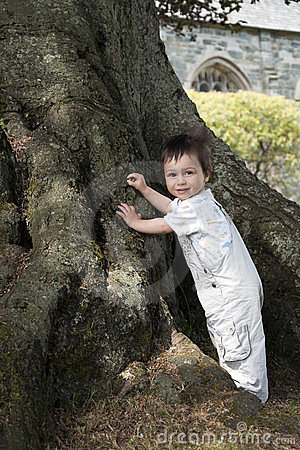 Toddler standing by tree