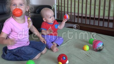 Todler broer en 4-jarige zus spelen thuis met kleurrijke ballen stock footage