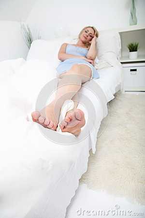 Toe to head view of woman on her bed