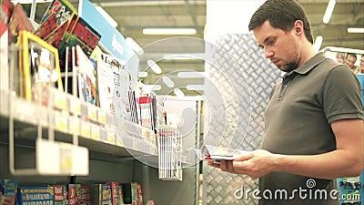 TOGLIATTI RYSK FEDERATION - JULI 07, 2017: Ung man som väljer en tidskrift stock video