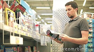 TOGLIATTI RYSK FEDERATION - JULI 07, 2017: Ung man som väljer en tidskrift lager videofilmer
