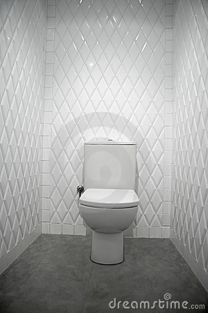 Toilet in a white room diamond shape tiles