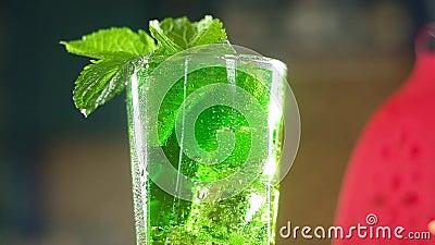 Toma panorámica de cóctel refrescante verde carbonatado con hojas de menta, cubos de hielo metrajes