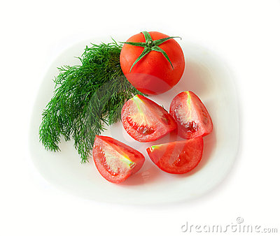 Tomato slices and dill on a plate. Isolated.