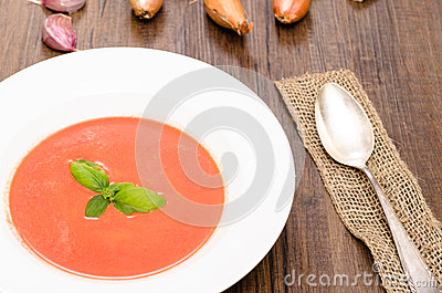 Tomato soup with basil and a spoon