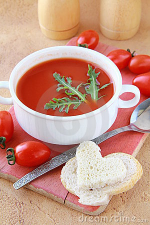 Tomato soup in a white bowl with arugula