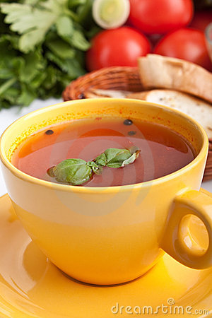Tomato soup in yellow cup with ingredients