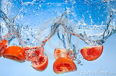 Tomato. Vegetables fall deeply under water with splash