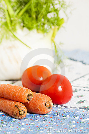 Tomatoes, carrots and fennel on blue tablecloth