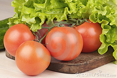 Tomatoes and salad on cutting board