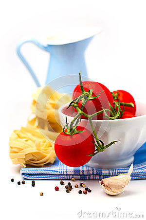 Tomatoes in white bowl and pasta